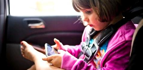 Kind spielt auf der Rückbank mit Handy
