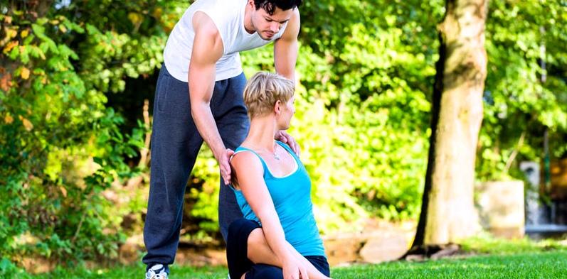 Ein Yogalehrer hilft seiner Schülerin