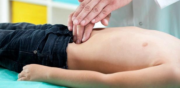 Ein Arzt tastet den Bauch eines Jungen ab
