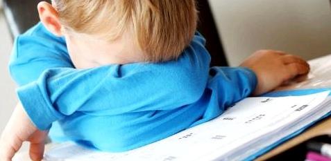 Ein Junge legt den Kopf auf den Schreibtisch