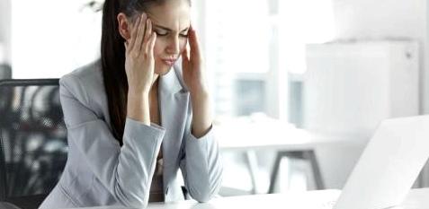 Frau reibt sich am Schreibtisch die Schläfen