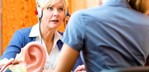 Eine Frau macht einen Hörtest beim Hörgerät-Akustiker