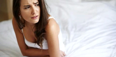 Frau mit Bauchschmerzen, Übelkeit und Blähungen