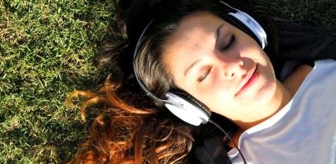 Eine Frau liegt im Gras und hört Musik