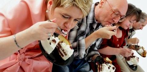 Erwachsene sitzen in einer Reihe und essen Torte