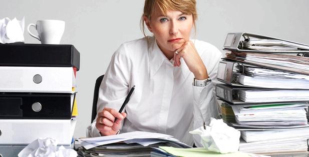 Eine Frau sitzt an ihrem Schreibtisch zwischen Papierbergen