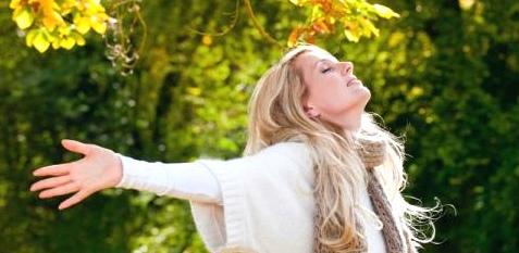 Eine Frau streckt sich der Herbstsonne entgegen
