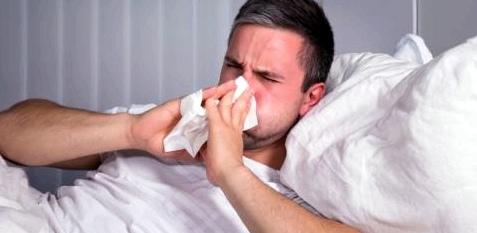 Mann liegt krank im Bett