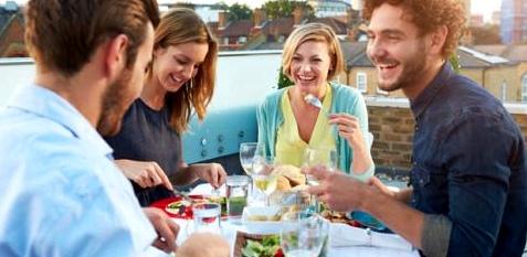 Freunde beim gemeinsamen Abendessen auf einer Dachterrasse