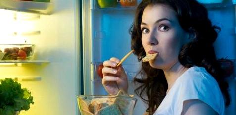 Frau isst nachts am Kühlschrank