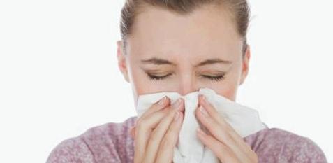 Frau hat Schnupfen und putzt sich die Nase