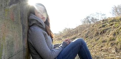 Ein Mädchen sitzt an eine Mauer gelehnt und schaut traurig