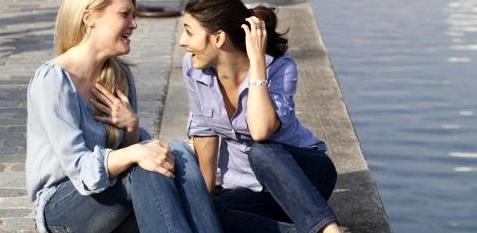 Zwei Freundinnen plaudern und lachen