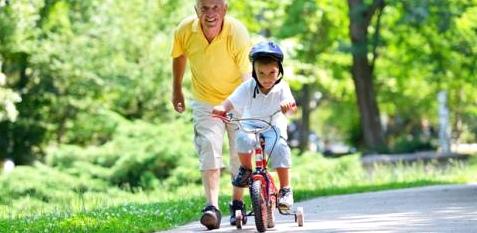 Ein kleiner Junge fährt Dreirad und sein Großvater läuft hinter ihm her
