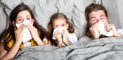 Eine Familie liegt krank im Bett
