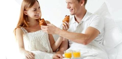 Ein Paar frühstückt im Bett