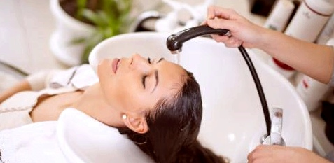 Eine Frau lässt sich beim Friseur die Haare waschen
