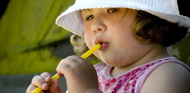 Ein übergewichtiges Mädchen trinkt aus einem Strohhalm