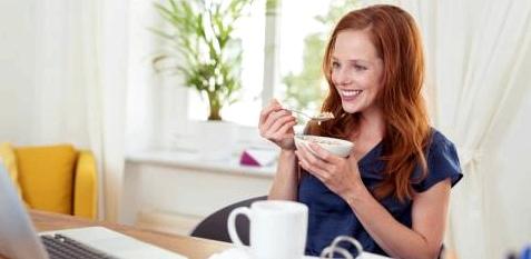 Frau isst Müsli vor dem Computer