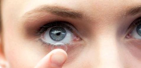 Eine Frau setzt sich Kontaktlinsen ein