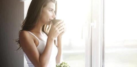 Eine Frau steht am Fenster und trinkt Kaffee