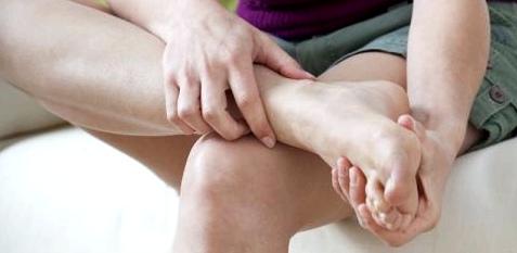 Eine Frau hält sich den Fuß