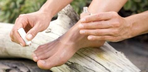 Frau lackiert sich die Fußnägel mit medizinischem Lack