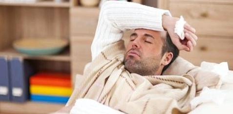 Mann liegt mit Erkältung auf dem Sofa