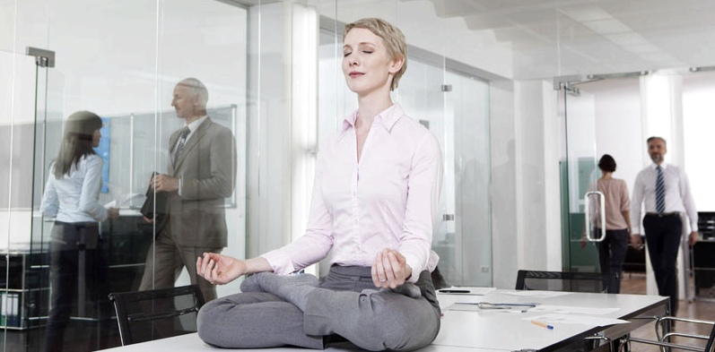 Frau macht Entspannungsübungen im Büro