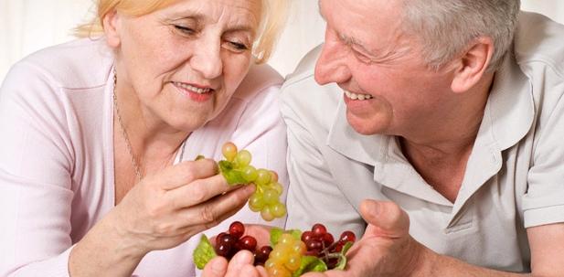 Ein älteres Pärchen isst Trauben