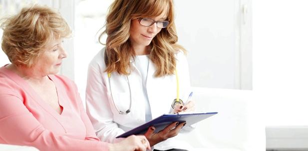 Eine Ärztin füllt mit einer älteren Patientin einen Fragebogen aus