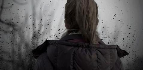 Eine Frau sieht in den Regen hinaus