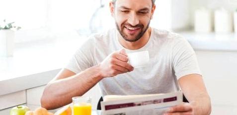 Ein Mann frühstückt und trinkt Kaffee