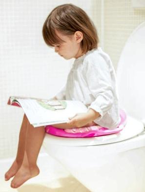 Mädechen liest auf der Toilette beim Toilettentraining