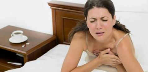 Eine Frau sitzt im Bett und hat Brustschmerzen