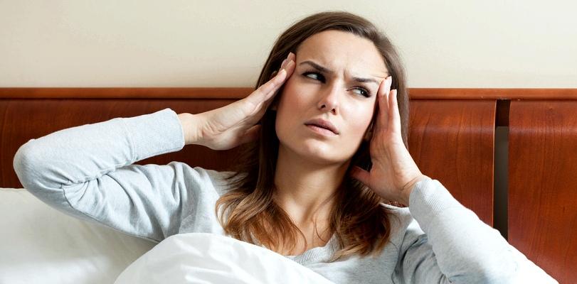 Frau mit Schwindel und Migräne im Bett