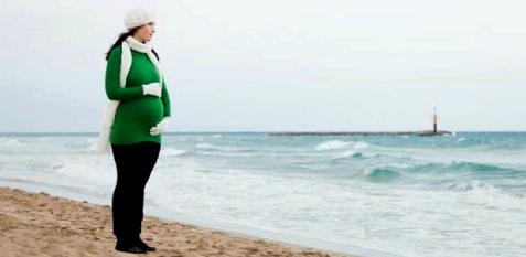 Eine schwangere Frau steht am Meer