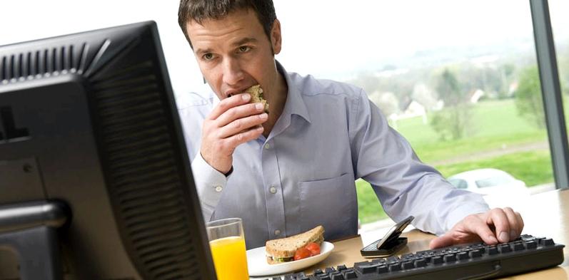 Mann isst während der Arbeit