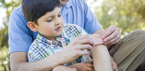 Ein Vater klebt seinem Sohn ein Pflaster aufs Knie