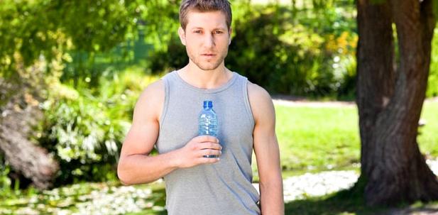 Ein Sportler hält eine Wasserflasche in der Hand